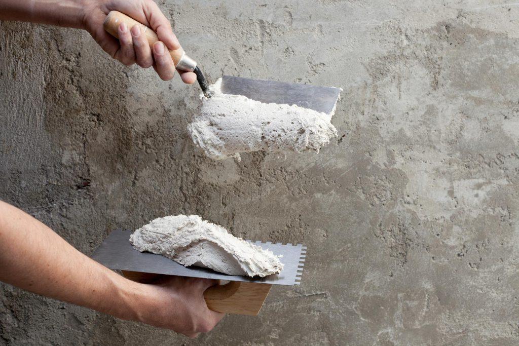 man puting stucco on the wall